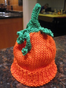 orange infant hat with green stem, leaf & vine