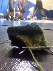 sock knit with Noro on gym floor with basketball game in background