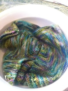 baby sweater soaking in bowl of water