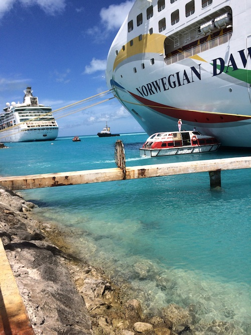 workers washing hull of cruise ship in port