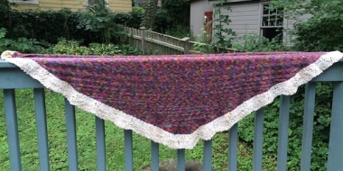 finished Bermudiana Shawl displayed on porch railing