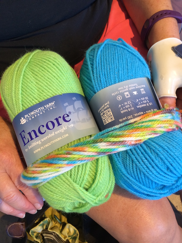 green and blue balls of yarn with sample of hand-dyed yarn