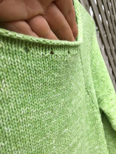 Detail of eyelet holes along neckline of sweater