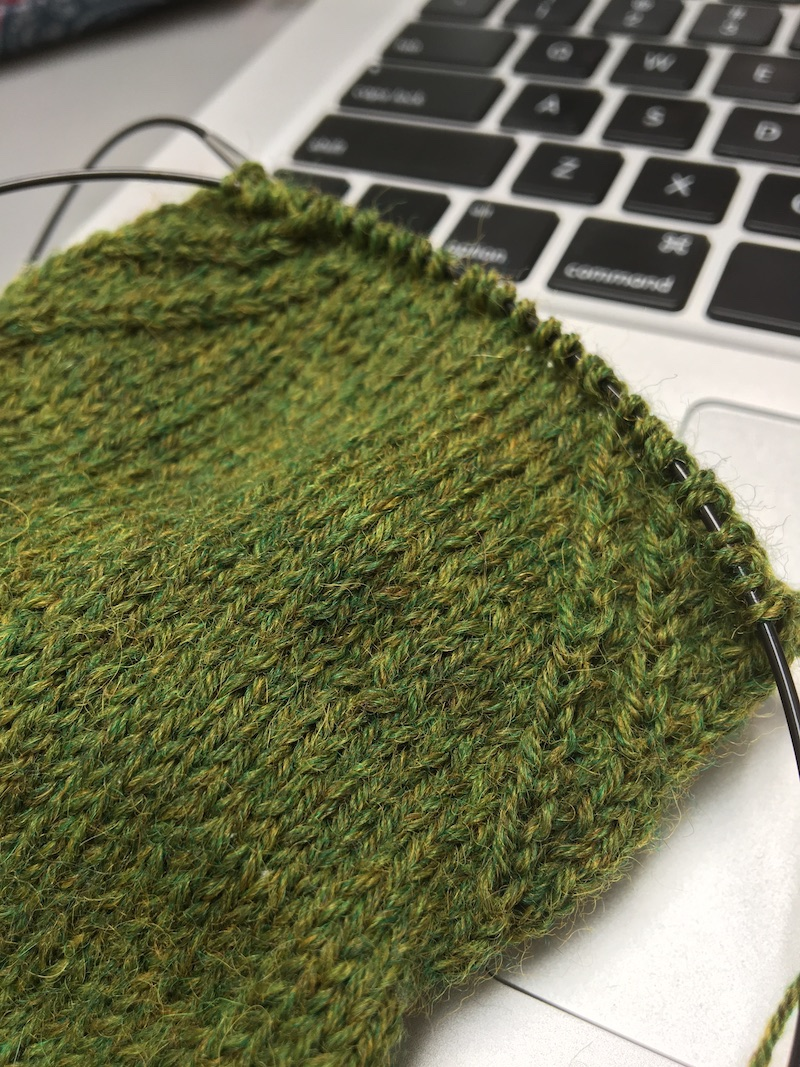 knitted sock in green yarn on circular needle, resting on laptop keypad