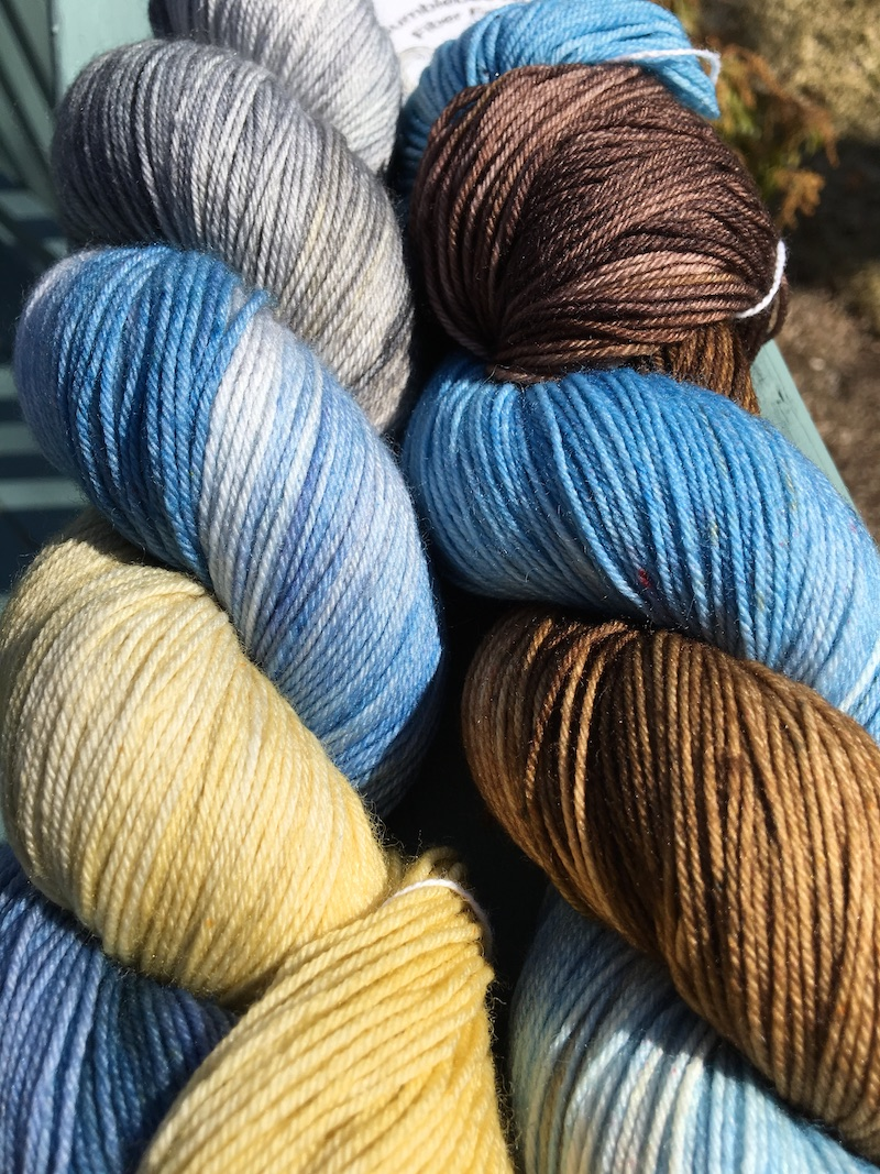 close up of two skeins of sock yarn in shades of blue, yellow, grey, and brown