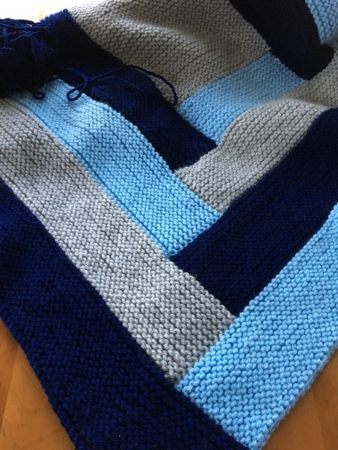 detail of knit log cabin blanket in grey, light blue, and navy