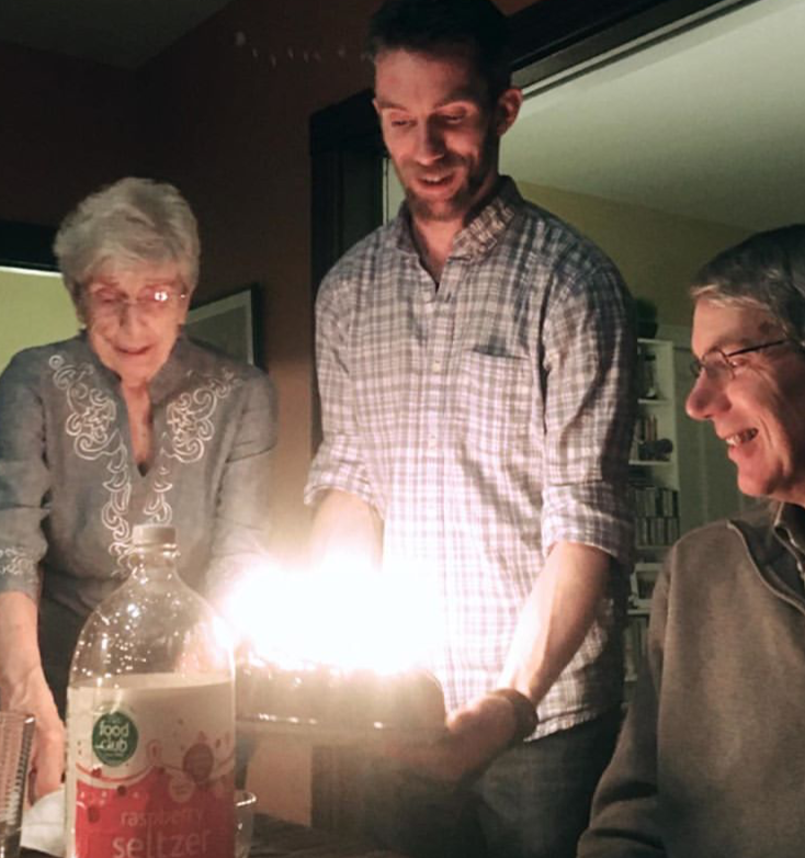 old woman, two men, holding birthday cake with candles