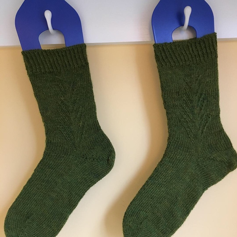 two green knit socks hanging on sock blocking frames