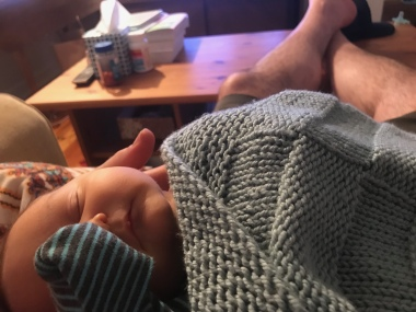 Baby wrapped in knit blanket and lying on man's lap