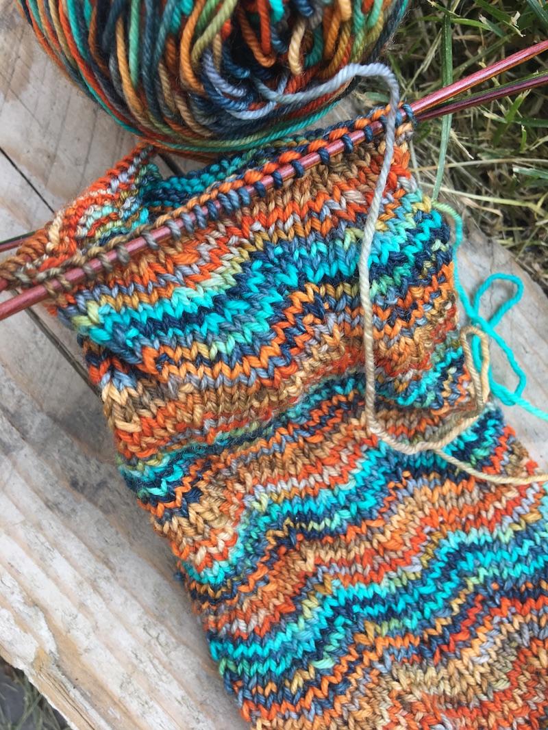 close up of knit sock in blue, green, orange yarn in chevron pattern