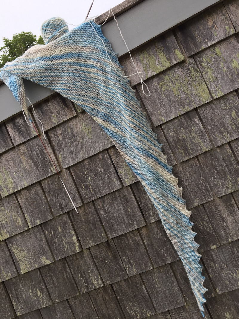 triangular knit scarf in blue white yarn hanging on grey shingle shed